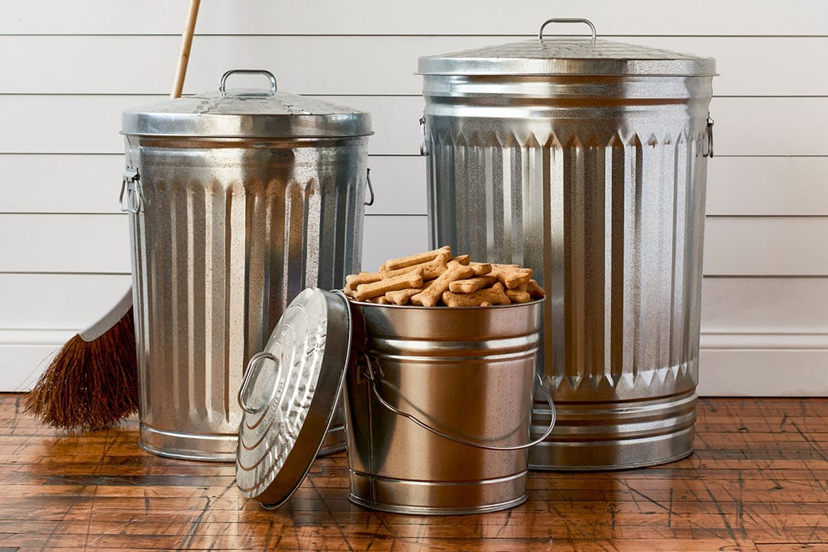 A short , medium, and large galvanized steel cans with dog food in the shortest can.