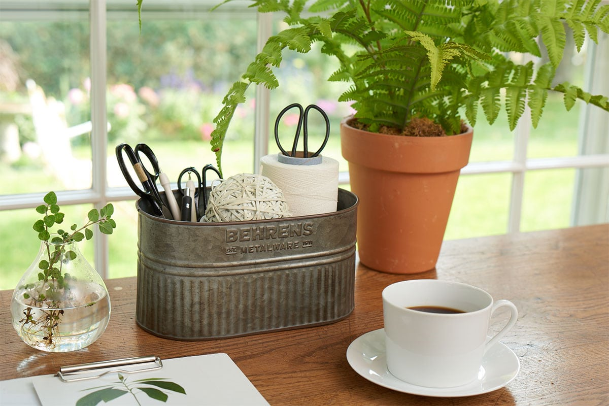 A window with a desk in front with a steel organizer tub with scissors and twine