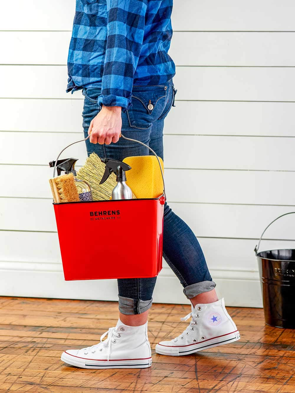 Person holding a red metal pail filled with cleaning supplies