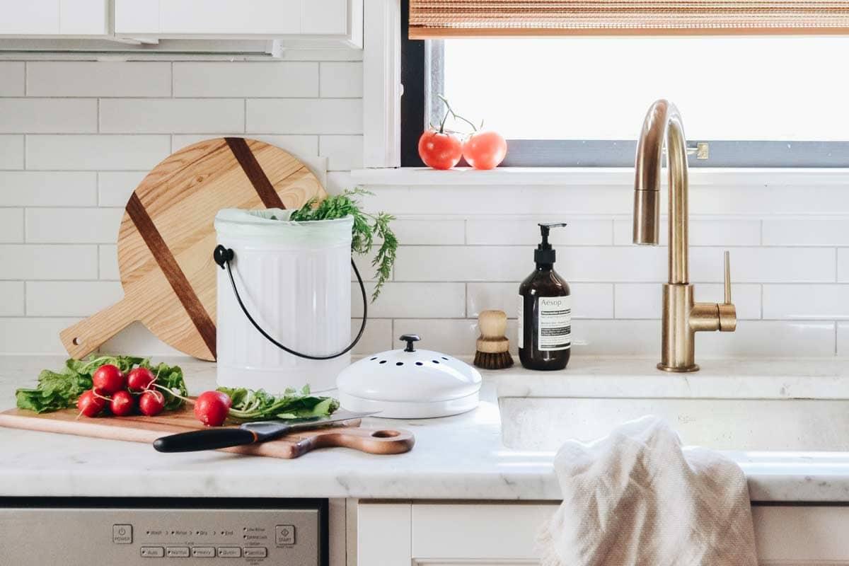White kitchen with a white galvanized compost pail next to veggies