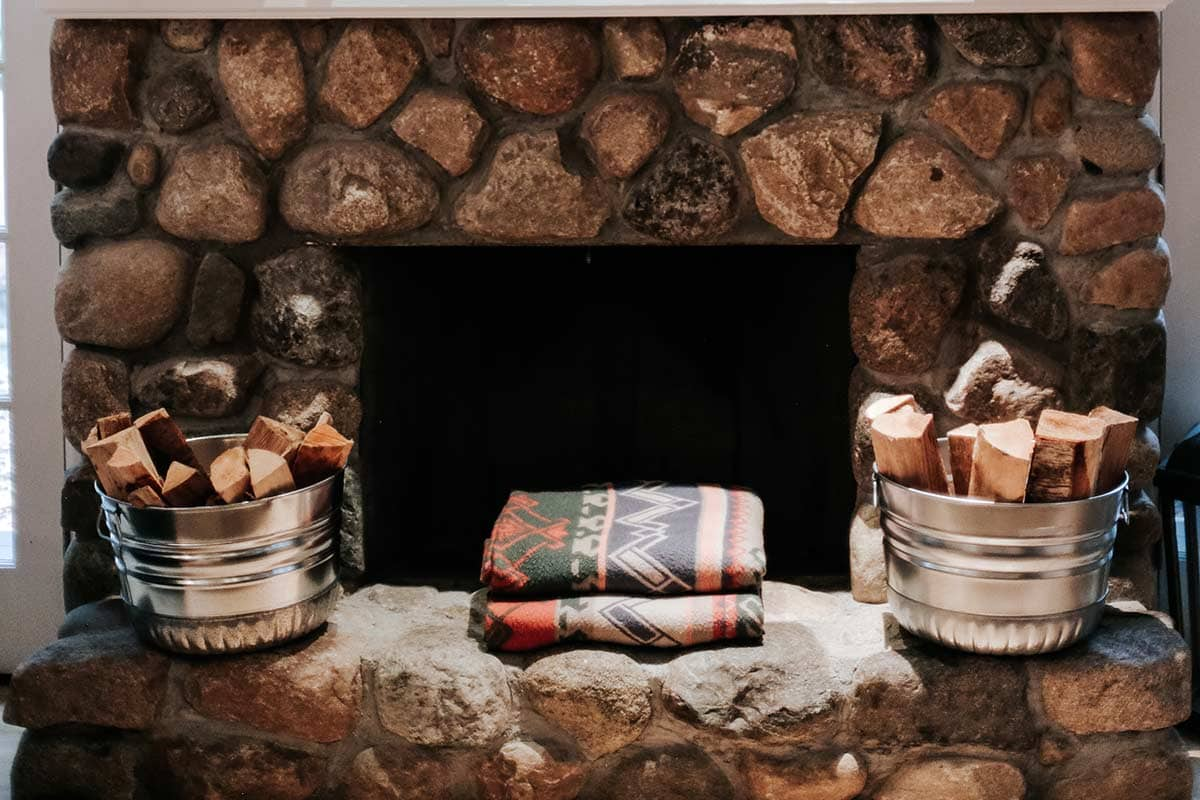 Galvanized steel tubs holding chopped wood on a fireplace mantel