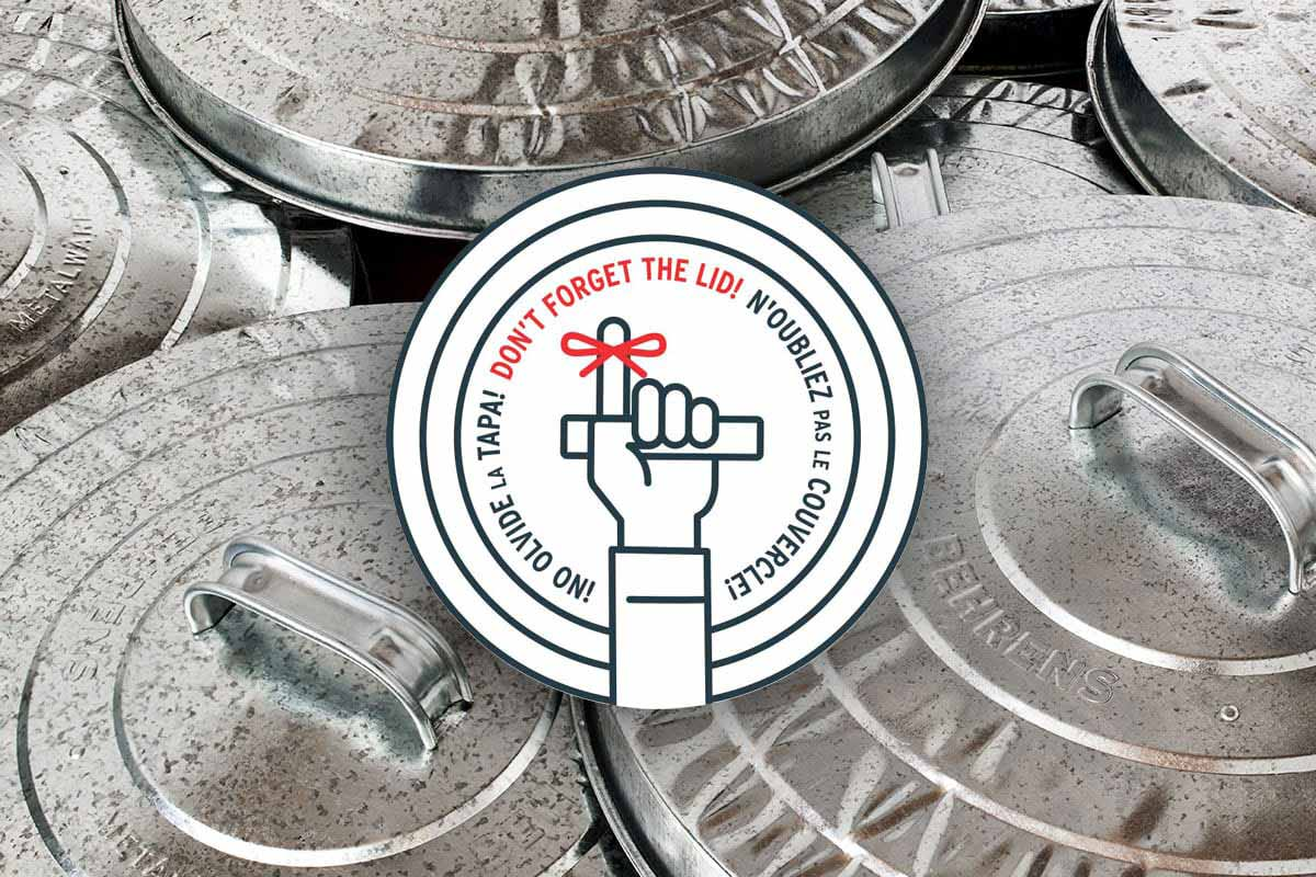 Galvanized steel trash can lids piles up with the Behrens logo.