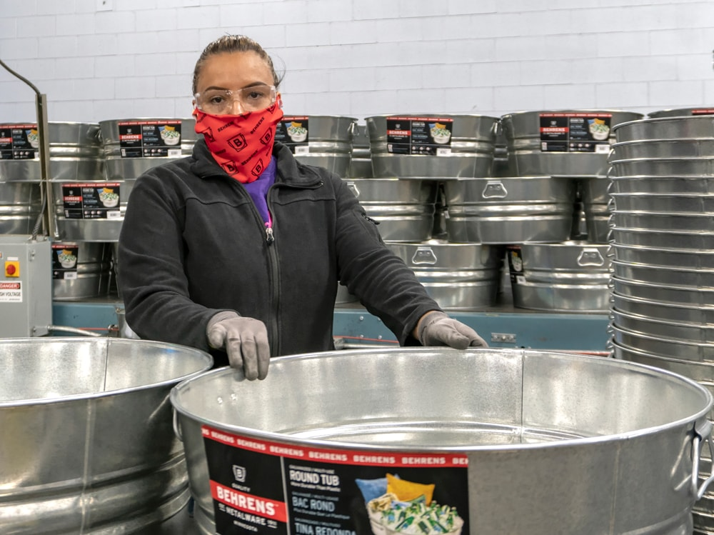 Behrens employee processing galvanized tubs